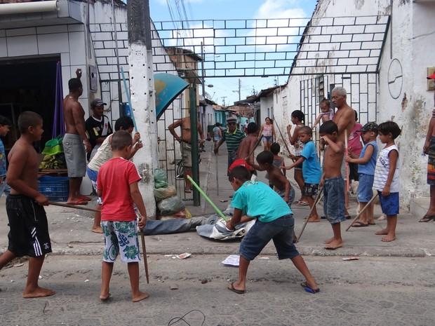Crianças se divertem na malhação de Judas sob a vigilância dos mais velhos. (Foto: Michelle Farias/G1)