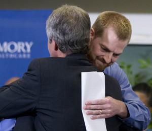 O médico americano Kent Bratly abraça um dos médicos que tratou dele nas últimas 3 semanas. Ele recebeu alta nesta quinta-feira (21) (Foto: AP Photo/John Bazemore)