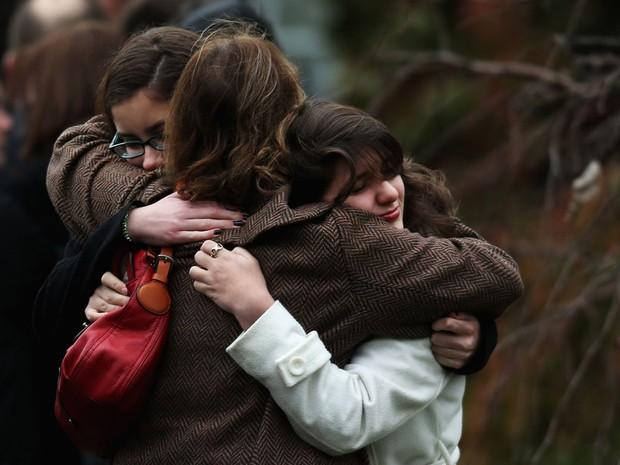 17 de dezembro - Mulheres se abraçam ao chegar para o funeral de Noah Pozner em Fairfield, morto no massacre em Newtown. (Foto: Spencer Platt/Getty Images/AFP)