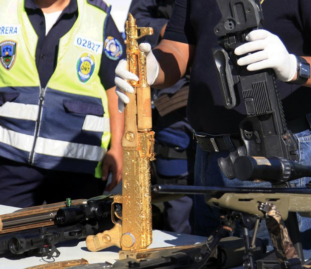 A polícia de Honduras mostrou neste sábado (5) diversos armamentos apreendidos em uma operação realizada na cidade de Choloma, entre eles um rifle AK-47 coberto de ouro. Segundo a mídia local, granadas e munições de vários tipos foram recolhidas. (Foto: Josue Banegas/Reuters)