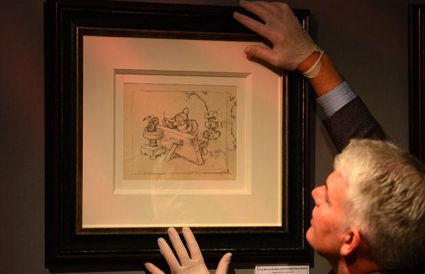 O consultor Duncan Phillips segura desenho de 1937 da Branca de Neve e os Sete Anões (Foto: Andrew Yates/AFP)