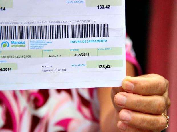 Dona de casa exibe conta com valor que seria injusto, segundo ela (Foto: Romulo de Sousa/G1 AM)