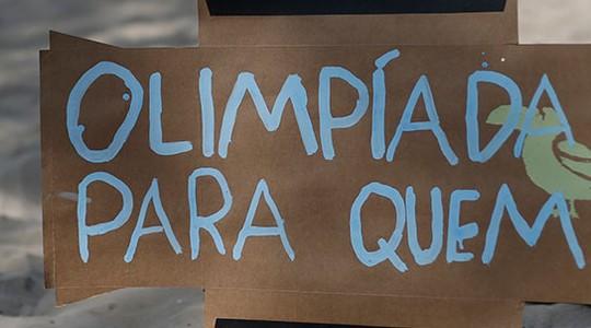 Placa de protesto contra as Olimpíadas na Praia de Copacabana, no Rio. Na semana passada, as Forças Armadas alertaram para o alto índice de presença de larvas de mosquito no entorno das instalações olímpicas na Barra da Tijuca  (Foto: Silvia Izquierdo/AP)