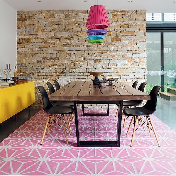 Tudo tem cor na sala de jantar: do tapete rosa aos pendentes, passando pelo aparador amarelo. O piso de concreto usinado com resina é mais neutro e fácil de limpar, ótimo para uma casa com crianças. Projeto da arquiteta Monica Drucker (Foto: Lufe Gomes/Casa e Jardim)