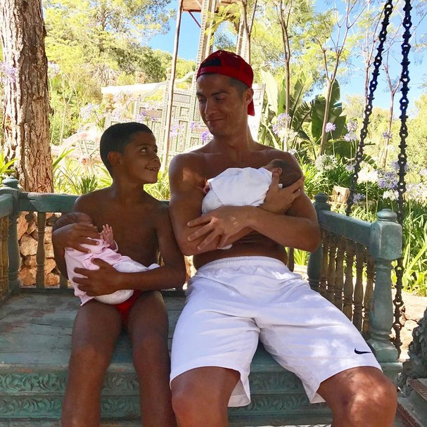 Está vendo os gêmeos fofinhos no colo de Cristiano Ronaldo e seu filho mais velho? Eles nasceram de barriga de aluguel (Foto: Instagram/Reprodução)