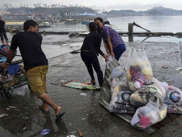 10/11 -Sobreviventes usam um telhado de aço para levar mantimentos e suprimentos na cidade de Tacloban (Foto: Aaron Favila/AP)