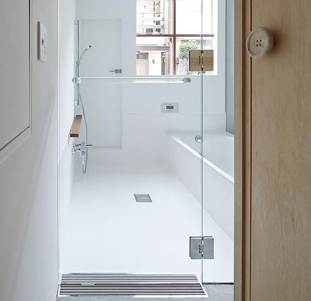 Até o banheiro é integrado, fechado apenas por portas de vidro. O vaso sanitário fica discreto atrás da estrutura de madeira que envolve a escada (Foto: Divulgação)