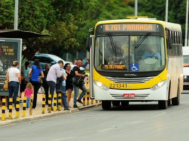 Ônibus parado no ponto enquanto as pessoas vão entrando