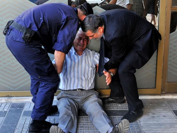 Idoso chora e é amparado em frente a agência bancária em Thessaloniki; saques foram limitados pelo governo e cartão de débito não é comum entre aposentados (Foto: Sakis Mitrolidis / AFP)