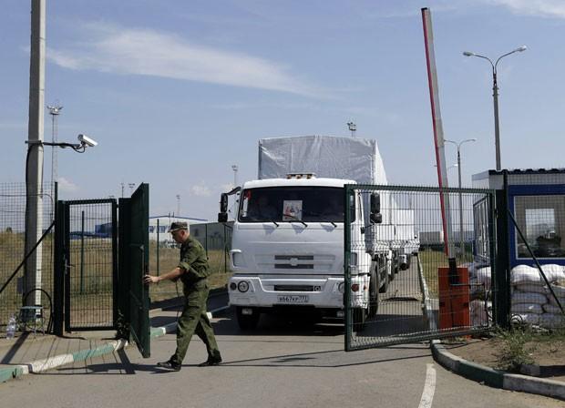 Guarda de fronteira russo abre portão nesta sexta-feira (22) para entrada na Ucrânia dos primeiros caminhões com ajuda humanitária enviados pela Rússia (Foto: Sergei Grits/AP)