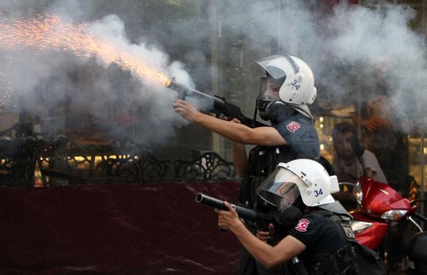 Polícia turca atira gás lacrimogênio contra os manifestantes para dispersar a aglomeração que se reunia na Praça Taksim, em Istambul, neste sábado (6) (Foto: Thanassis Stavrakis/Associated Press)