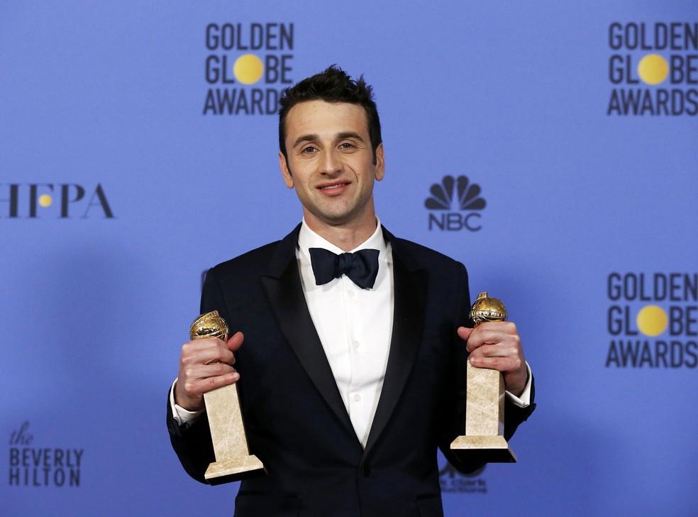 O compositor Justin Hurwitz segura os dois troféus que ganhou no Globo de Ouro 2017: melhor canção original, pela música 'City of stars', e melhor trilha sonora, ambas do filme 'La la land: Cantando estações' (Foto: Mario Anzuoni/Reuters)