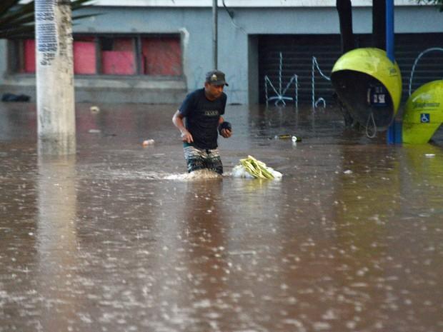 Homem caminha em área alagada na região do Terminal Praça Antônio Menck, no centro de Osasco, após o temporal que atingiu a cidade no final da tarde desta quarta (22). (Foto: Renato Silvestre/Estadão Conteúdo)
