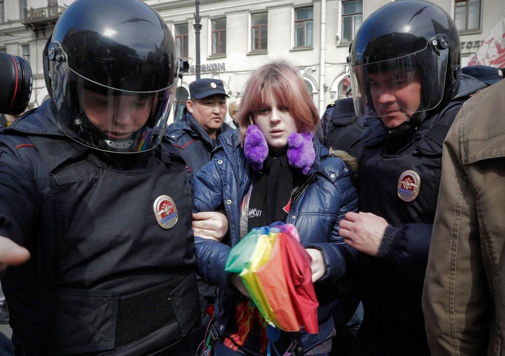 Ativista gay que segurava um guarda-chuva com as cores da bandeira LGBT é detida pela polícia durante marcha do Dia do Trabalhador no centro de São Petersburgo, na Rússia, nesta segunda-feira, dia 1º de maio de 2017 (Foto: Dmitri Lovetsky/AP)