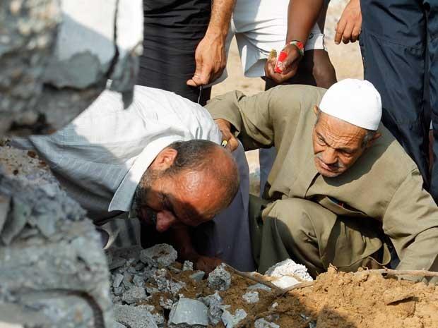 Equipes de resgate palestinas procuram vítimas em um prédio destruído por um ataque aéreo israelense em Rafah. (Foto: Said Khatib / AFP Photo)
