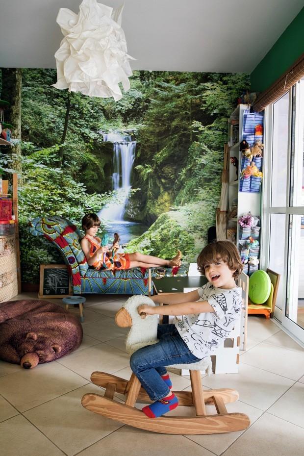 Zoe e Zion se divertem na brinquedoteca. O papel de parede de cachoeira é da Leroy Merlin. Ao fundo, chaise longue da família de Teka, forrada com tecidos africanos (Foto: Lufe Gomes / Editora Globo)