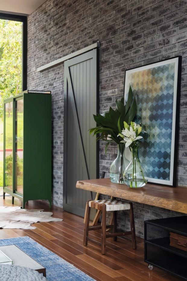 Entrada. Cristaleira laqueada de verde (M050, da Sayerlack), com desenho da Two Design. Aparador da Tora Brasil com vidros e banquinho da Dpot Objeto. Quadro da Urban Arts (Foto: Evelyn Müller / Divulgação)