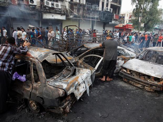 Pessoas observam o local em um centro comercial após um ataque suicida com explosivos em Bagdá, no Iraque (Foto: Khalid al Mousily/Reuters)