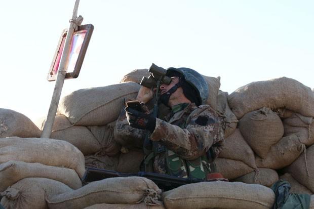 Combatente curdo usa binóculo durante ofensiva contra o Estado Islâmico em Sinjar nesta quinta-feira (12) (Foto: Ari Jalal/Reuters)