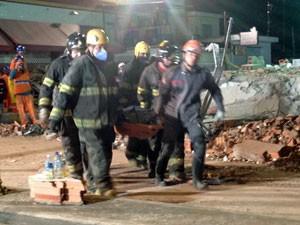 Mais um corpo é retirado dos escombros na noite desta terça (Foto: Marcelo Mora/G1)