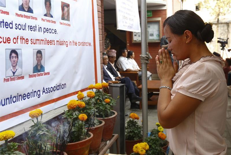 Viúva de uma das vítimas da avalanche no Monte Everest reza diante dos retratos dos mortos durante uma cerimônia em memória às vítimas. Pelo menos 16 pessoas morreram na avalanche do dia 18 de abril
