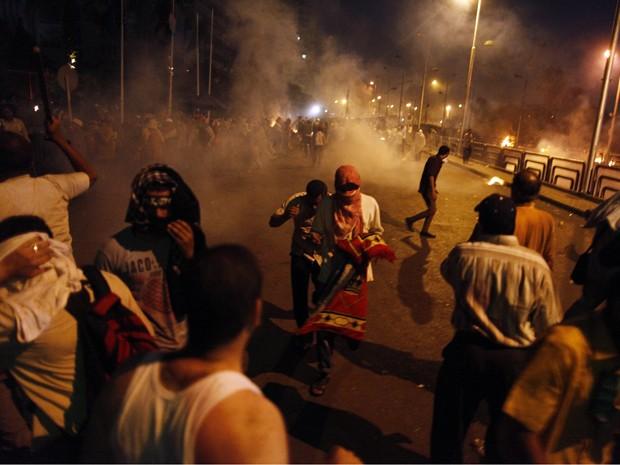 Pessoas correm no Cairo para se esconder de um tiroteiro na madrugada de segunda-feira (8) (Foto: Khaled Mahmoud/ AFP)