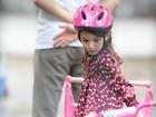 Suri Cruise anda de bicicletinha em parque de Nova York