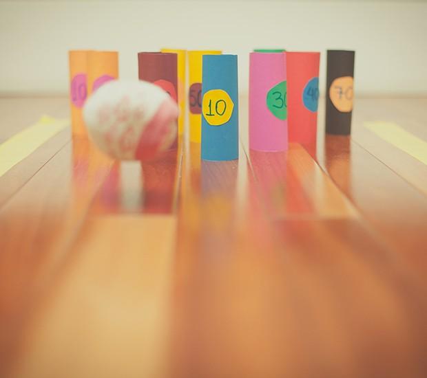 Strike! Rolinhos de papelão, papel colorido e uma bola de meia é tudo que você vai precisar para montar uma pista de boliche em casa. Para deixar a disputa mais animada, estabeleça pontos para cada rolinho (Foto:  Tati Abreu/Editora Globo)
