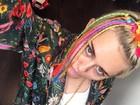 Miley Cyrus posa com acessórios coloridos e faz careta para fotos