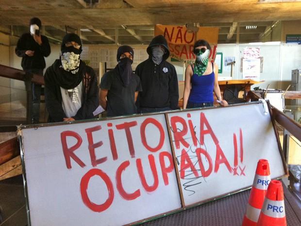 Mascarados fechando o acesso à reitoria da Universidade de Brasília (Foto: Isabella Formiga/G1)