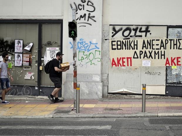 Pessoas caminham em rua com diversos comércios fechados em Atenas.  (Foto: LOUISA Gouliamaki / AFP)
