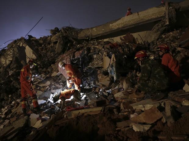 Bombeiros buscam vítimas do deslizamento. (Foto: Associated Press)