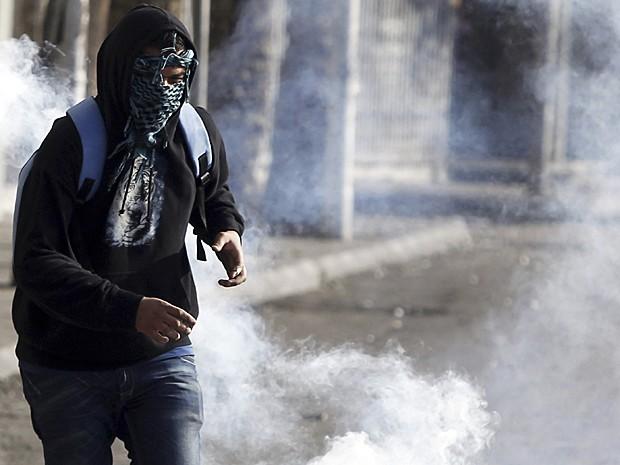 Manifestante contra presidente egípcio Mohamed Mursi tenta se livrar do gás lacrimogêneo na ponte Qasr Al Nil, perto da Praça Tahir, no Cairo (Foto: Amr Abdallah Dalsh/Reuters)