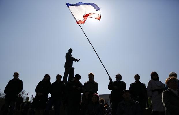 Homem carrega a bandeira da Crimeia um dia antes do referendo em Simferopol, em um protesto pró-Rússia (Foto: Thomas Peter/Reuters)