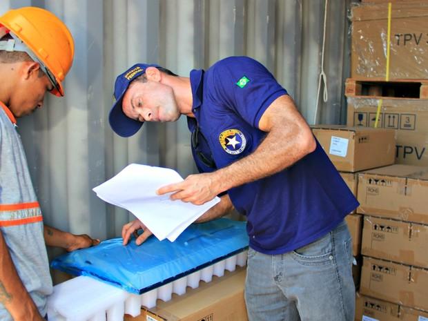Auditores analisam documentos e confrontam com produtos em Operação Padrão (Foto: Ísis Capistrano/ G1)