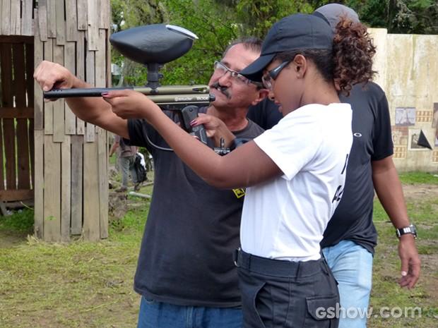 Erika recebe orientações do instrutor de tiro nos bastidores (Foto: Em Família)