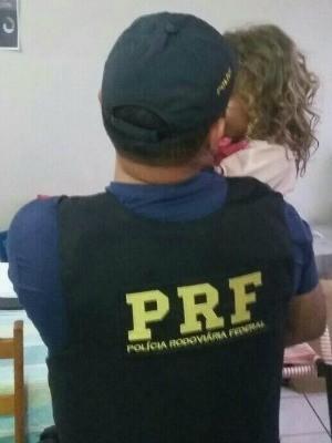 Policial com a menina após resgate (Foto: PRF/Divulgação)