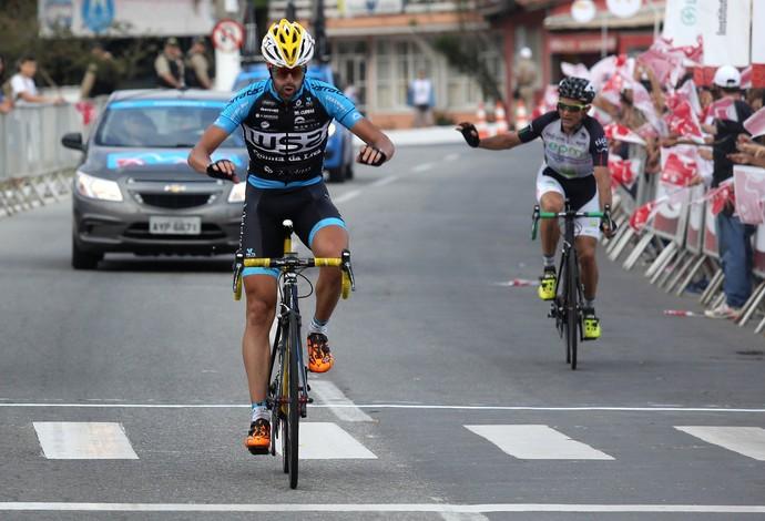 Gustavo Veloso cruza linha de chegada em primeiro, ao lado de Oscar Sevilla, mas é punido na 1ª etapa do Tour do Rio e perde liderança (Foto: Divulgação)