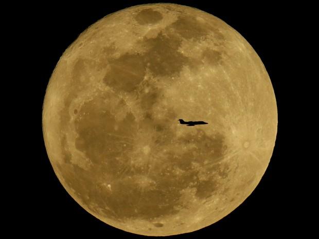 Silhueta de avião é vista em frente à lua no céu de Phoenix, nos EUA. (Foto: Charlie Riedel/AP)