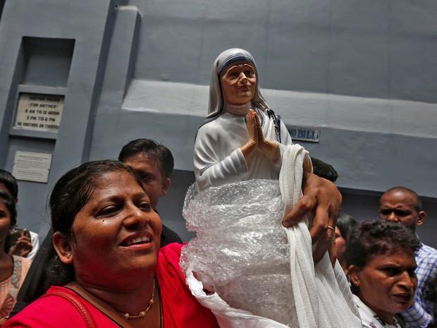 Fiel ergue estátua da Madre Teresa do lado de fora de uma filial das Missionárias da Caridade em Calcutá, na Índia, enquanto ela era canonizada neste domingo (4) em cerimônia no Vaticano (Foto: REUTERS/Rupak De Chowdhuri)
