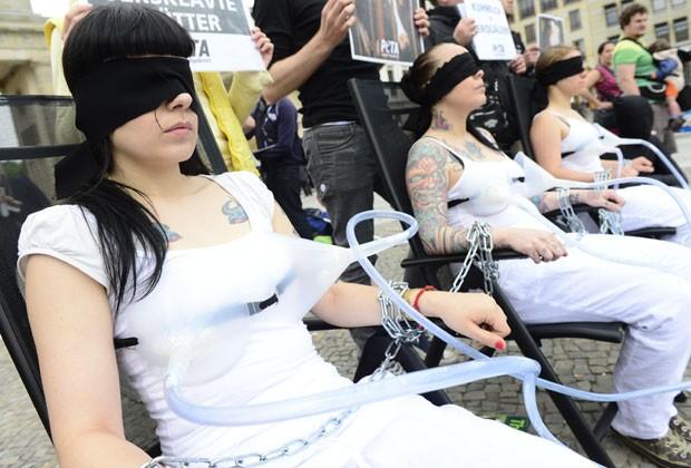 Ativistas do Peta posam com funis de sucção nos seios em Berlim nesta terça-feira (4); protesto é contra a indústria do leite (Foto: John Macdougall/AFP)