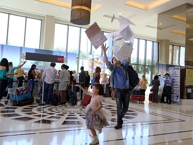 A pequena Bella faz com que os desenhos de Caíque se espalhem pelo aeroporto (Foto: Pedro Paulo Figueiredo/TV Globo)