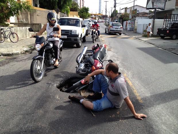 """Um homem que conduzia  sua moto acabou caindo em buraco na avenida Boto de Menezes, no bairro Tambiá, por volta das 12h30 desta terça-feira (14). Em forma de protesto, Paulo César Fialho, não retirou sua moto do buraco, o que acabou resultando em um grande congestionamento. """"Vou tirar algumas fotos para fazer um Boletim de Ocorrência para entrar com uma ação pedindo uma reparação de danos"""", disse Paulo César. A prefeitura informou que vai entrar com um pedido de reparação na avenida, e que o problema deve ser resolvido o mais rápido possível. (Foto: Walter Paparazzo/G1)"""