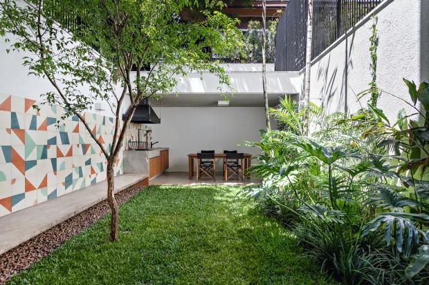 No pequeno jardim com paisagismo de Rodrigo Oliveira, o destaque é o banco de concreto que começa como bancada na cozinha e termina como churrasqueira na varanda gourmet (fundos) (Foto: Alessandro Guimarães / Divulgação)