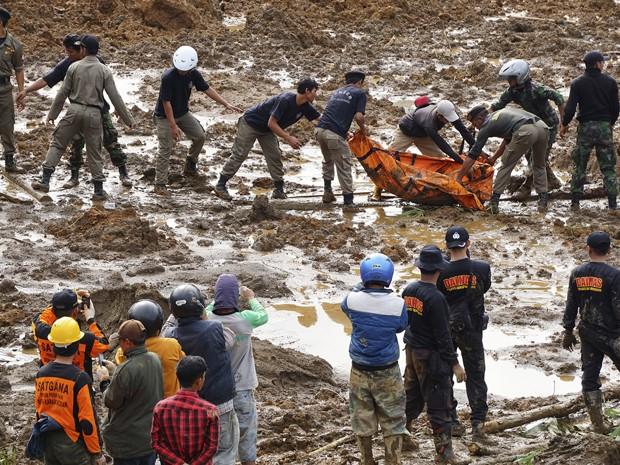 Equipe de resgate retira corpo de uma vítima de deslizamento em Jemblung, no centro de Java, na Indonésia (Foto: AP Foto/Bayu Nur)