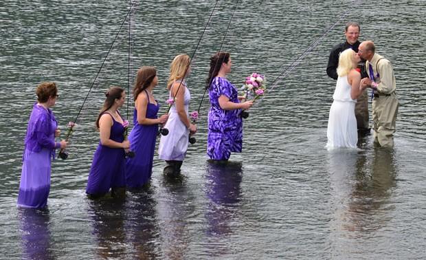 Acompanhado pelos padrinhos, um casal inovou no último sábado (3) e se casou no rio Buskin enquanto todos pescavam em Kodiak (Foto: James Brooks/Kodiak Daily Mirror/AP)