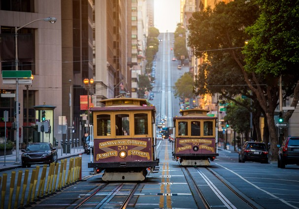 Classic view of historic traditional Cable Cars riding on famous California Street in beautiful early morning light at sunrise in summer, San Francisco, California, USA (Foto: Getty Images/iStockphoto)