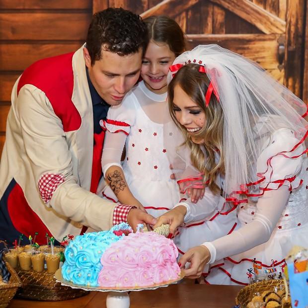 Casal parte o bolo para descobrir sexo do segundo filho. Recheio rosa indica que terão uma menininha. (Foto: Manuela Scarpa/Brazil News)