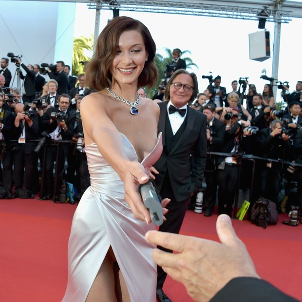 "CANNES, FRANCE - MAY 17:  Bella Hadid smiles as she picks up a camera battery which a photographer dropped on the red carpet, before giving it back as she attends the ""Ismael's Ghosts (Les Fantomes d'Ismael)"" screening and Opening Gala during the 70th ann (Foto: Getty Images)"