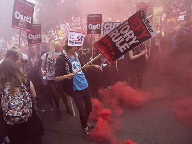 Manifestante chuta bomba de gás durante protesto contra austeridade em Londres, no sábado (20) (Foto: AFP Photo/Justin Tallis)